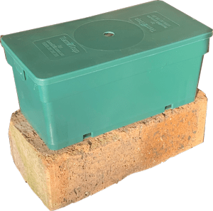 Piece of a wall brick with a green plastic box of a termite trap placed on top of it.