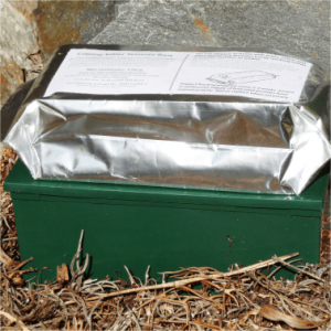 A green colored termite trap box with a termite bag placed on top.