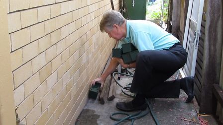 """A man (Ion Staunton) placing a green boxes of termite traps around a building that represents the """"place of monitors in termite defence"""" blog."""